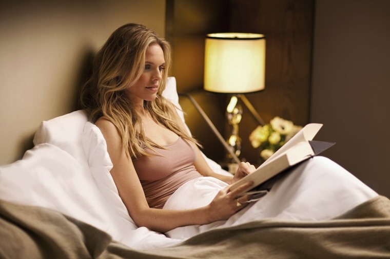 woman reading in bed with lamp turned on